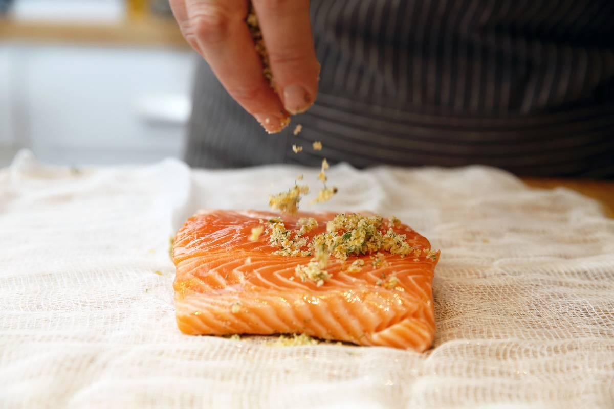 A chef sprinkles seasoning on a salmon filet.