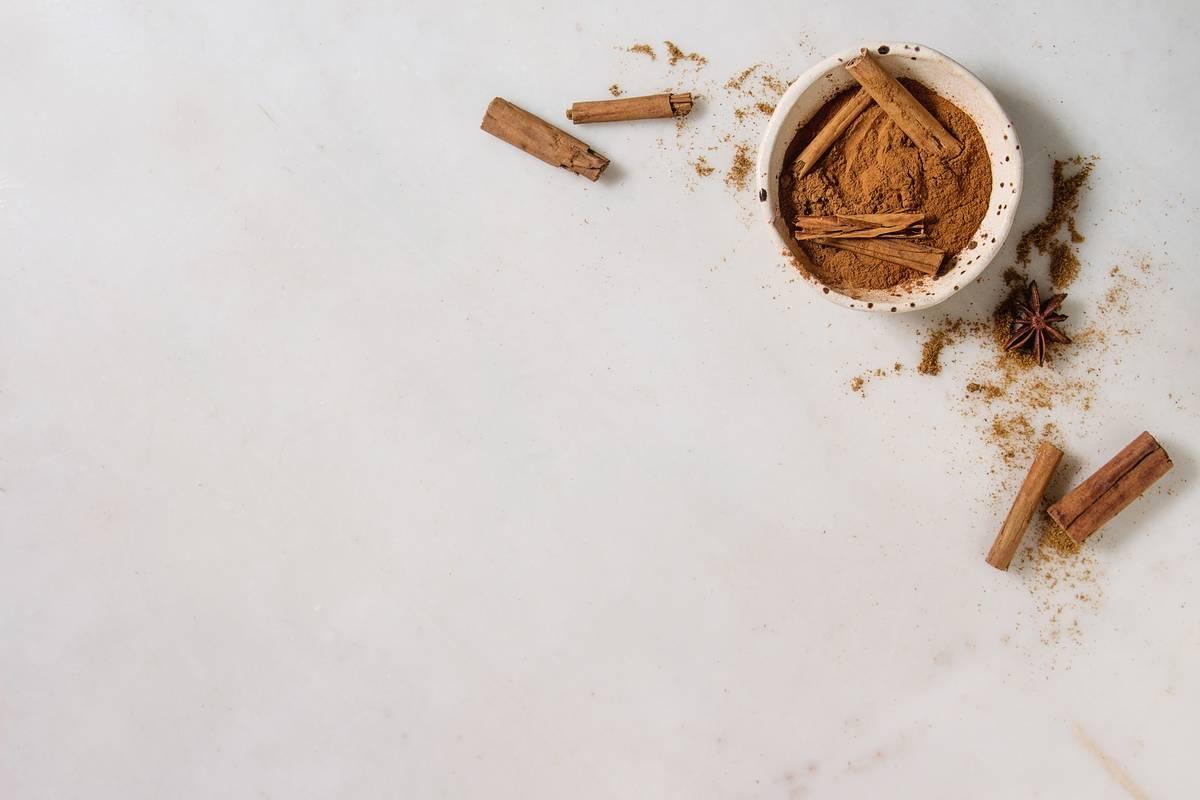 Cinnamon powder is in a bowl next to cinnamon sticks.
