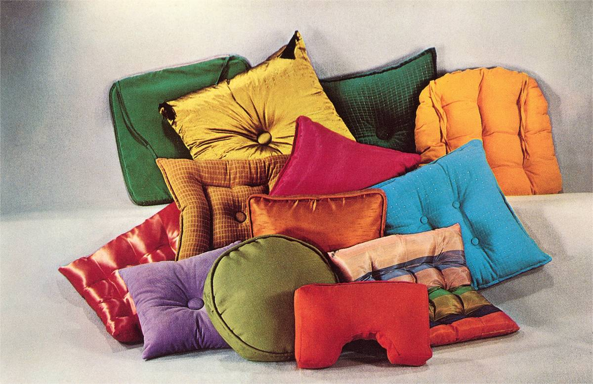 A pile of decorative pillows with different fabrics.