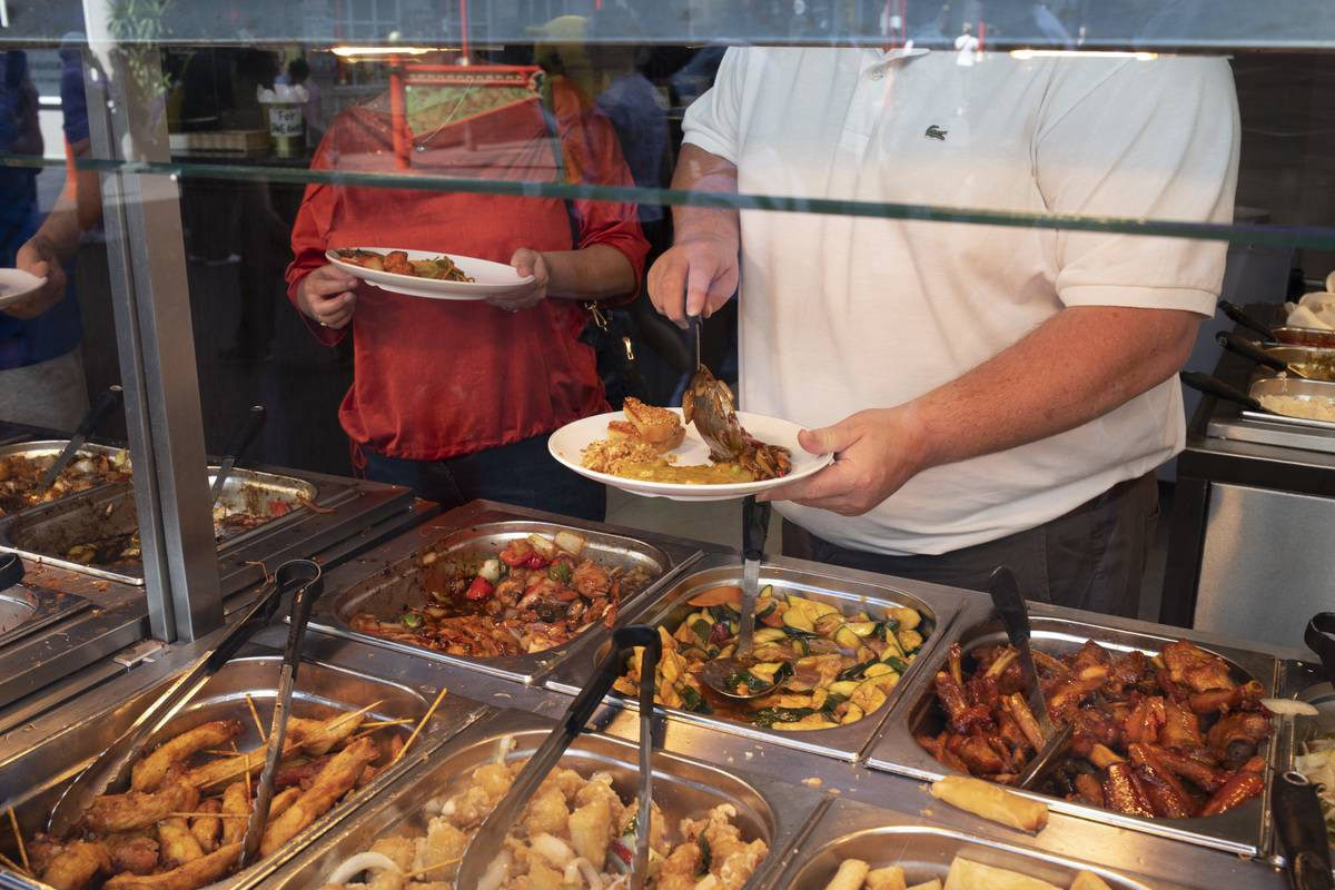 Customers pile food on their plates at a buffet.