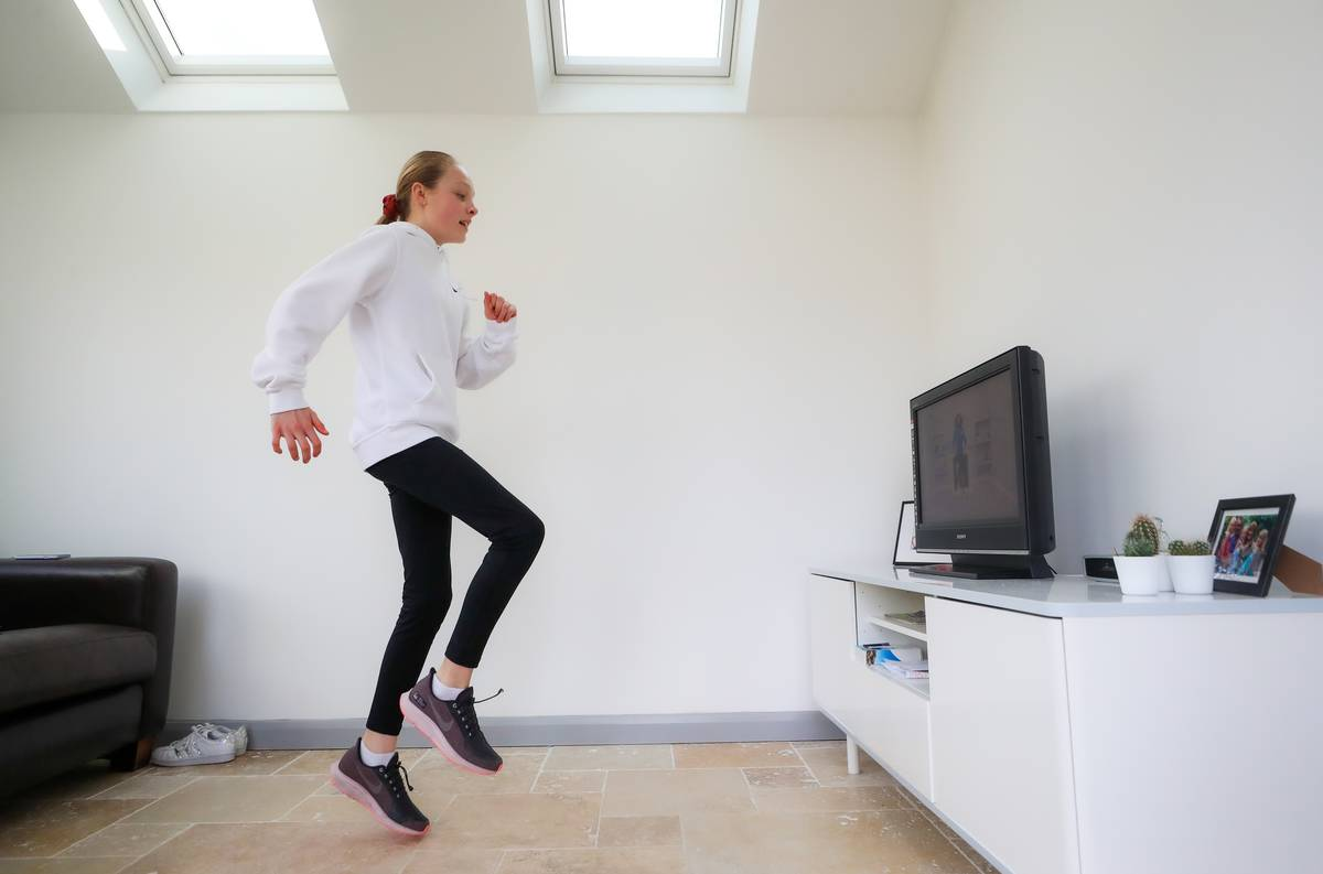 A girl exercises indoors while following a workout tape.