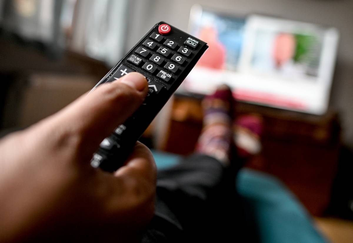 A person uses a remote while watching television.