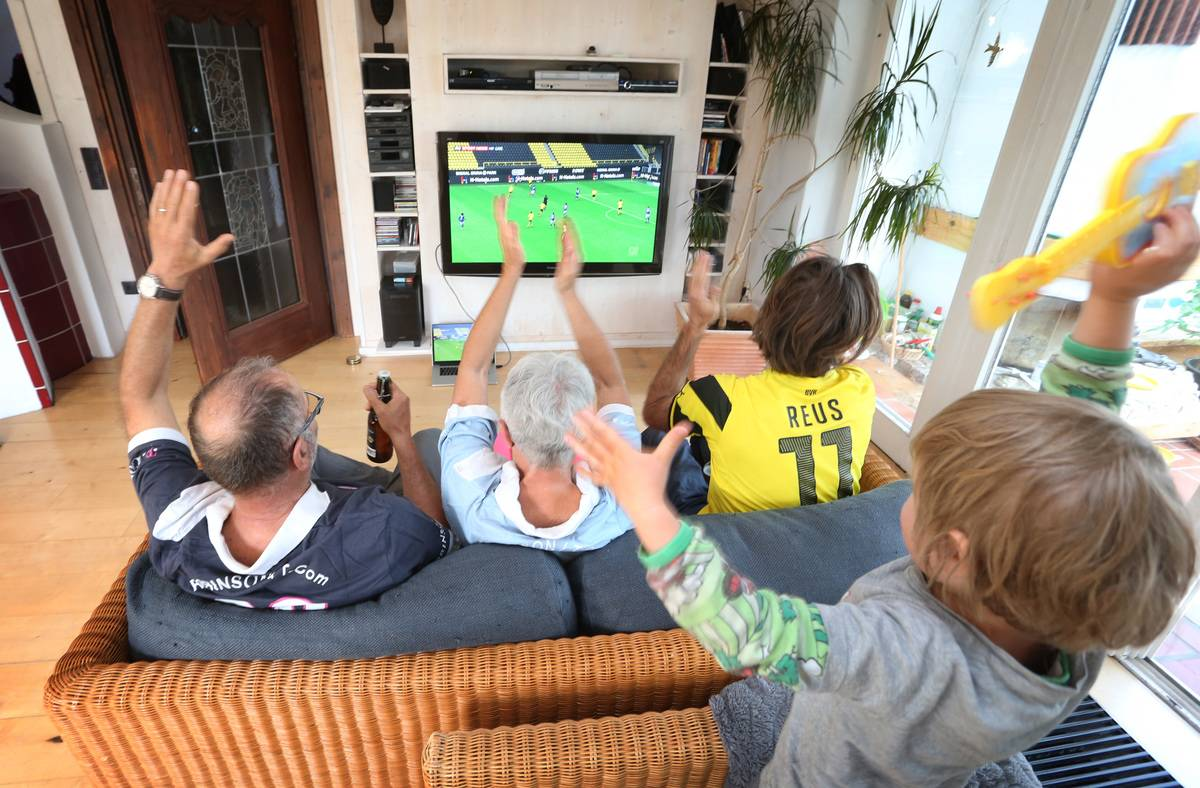A family watches a sports game on the TV.