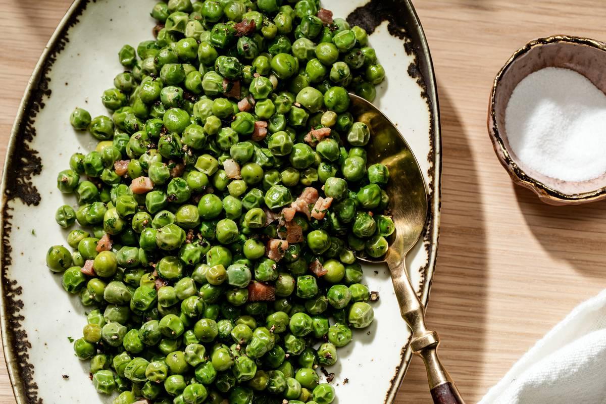 A spoon dips into a bowl of sautéed peas.