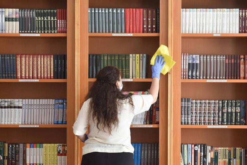 A member of staff wipes bookcases with a cloth at the Plaza Medical & Spa hotel.