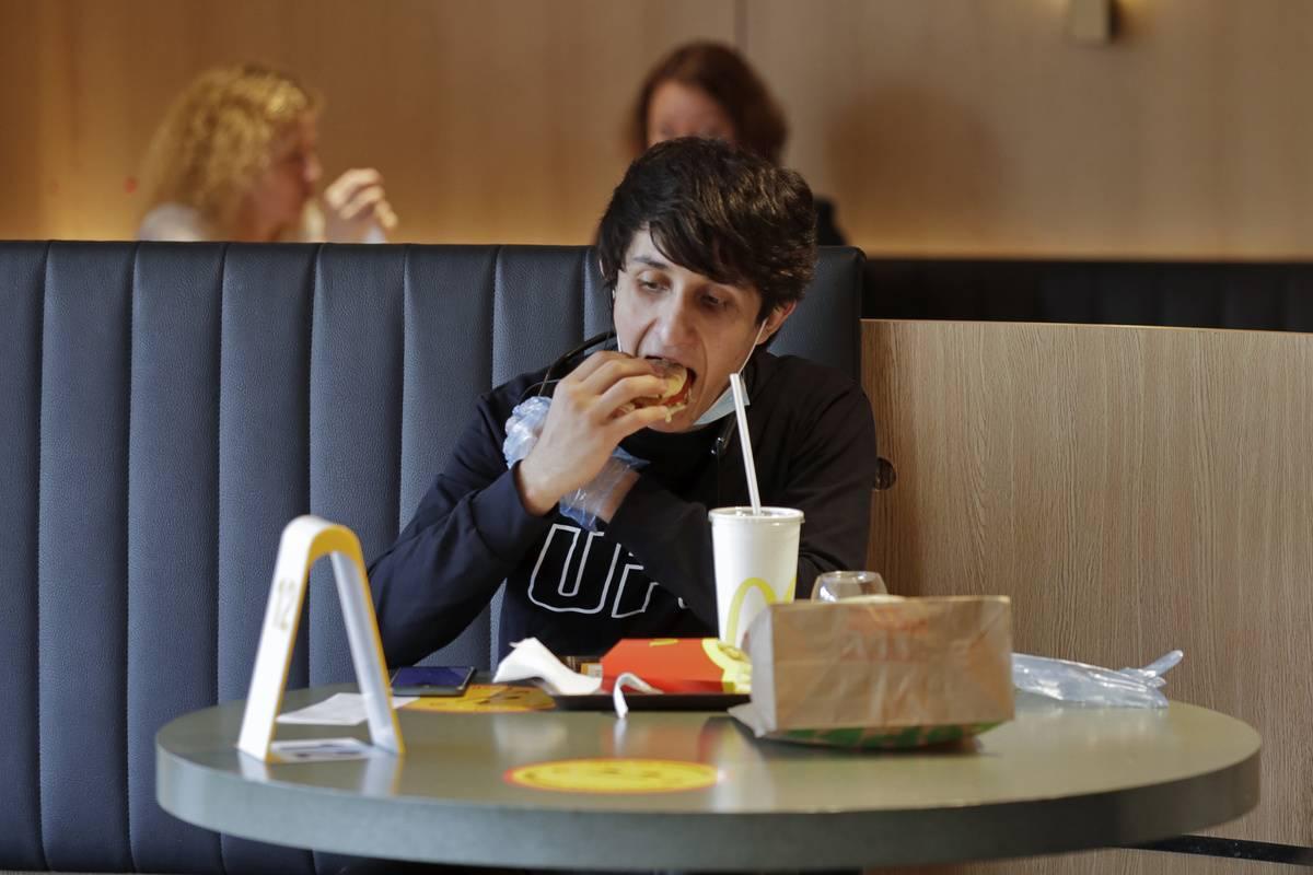 A man eats McDonald's in the restaurant.