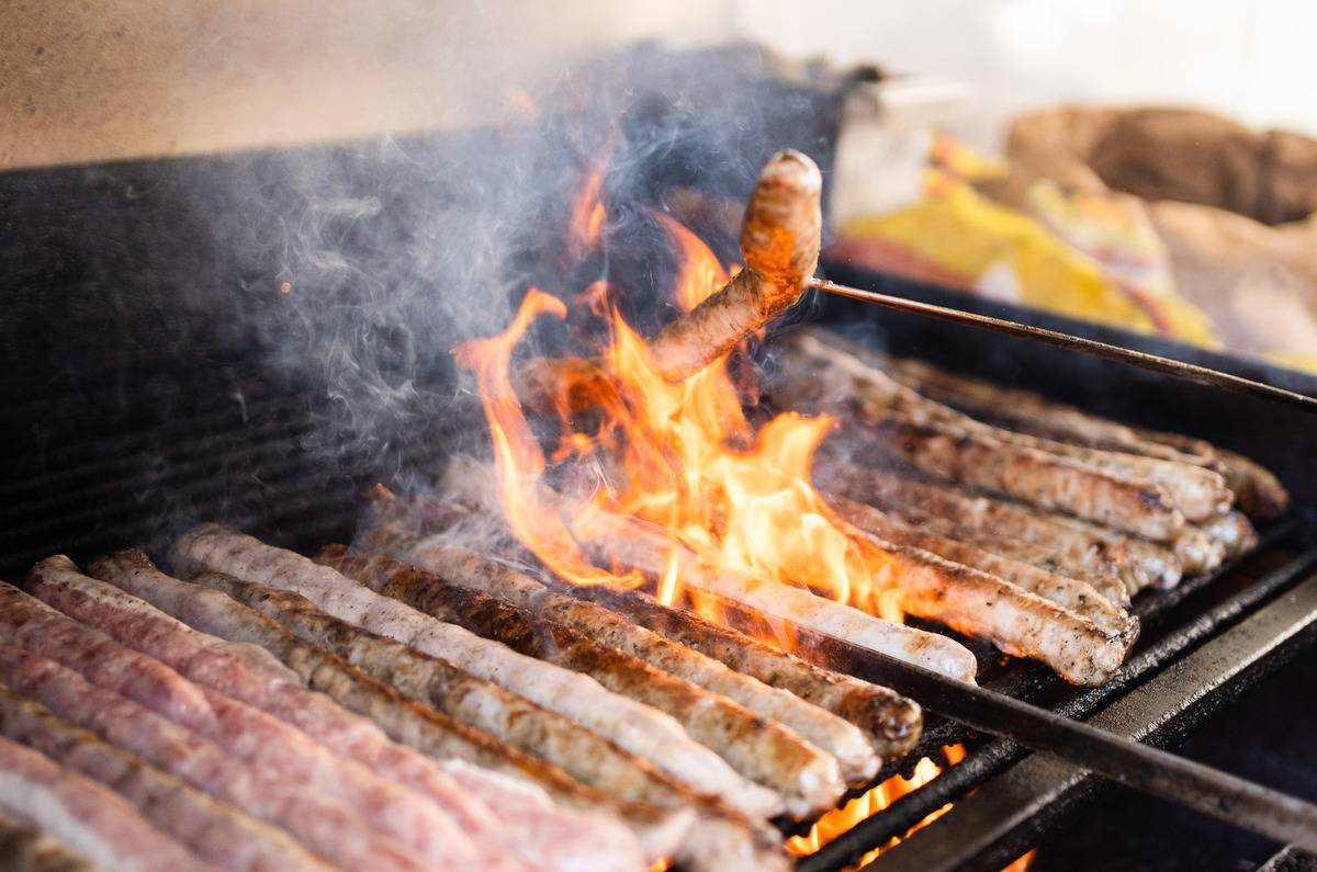 A chef flips a sausage on a flaming grill.