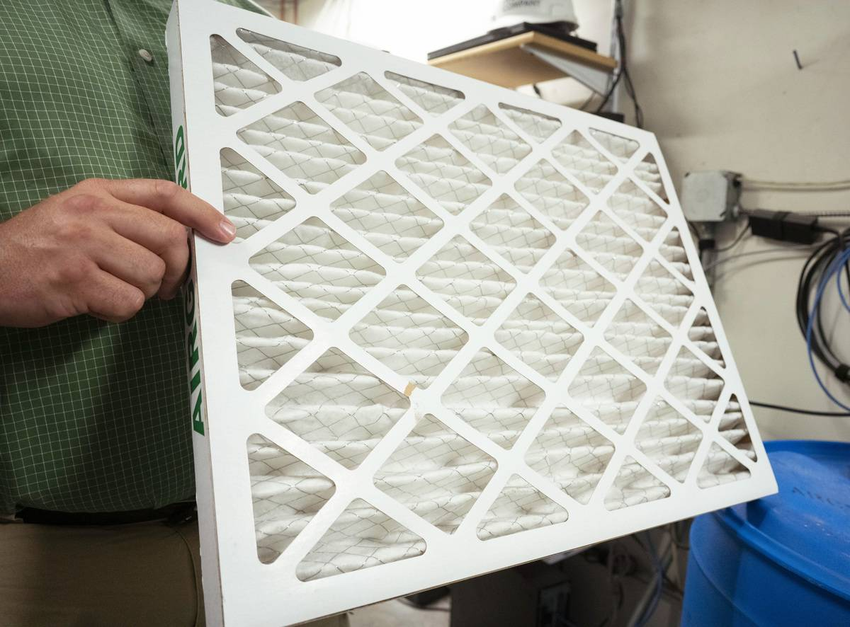 A person holds a HVAC filter.