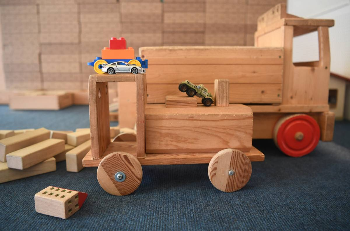Wooden toys and toy cars are pictured.