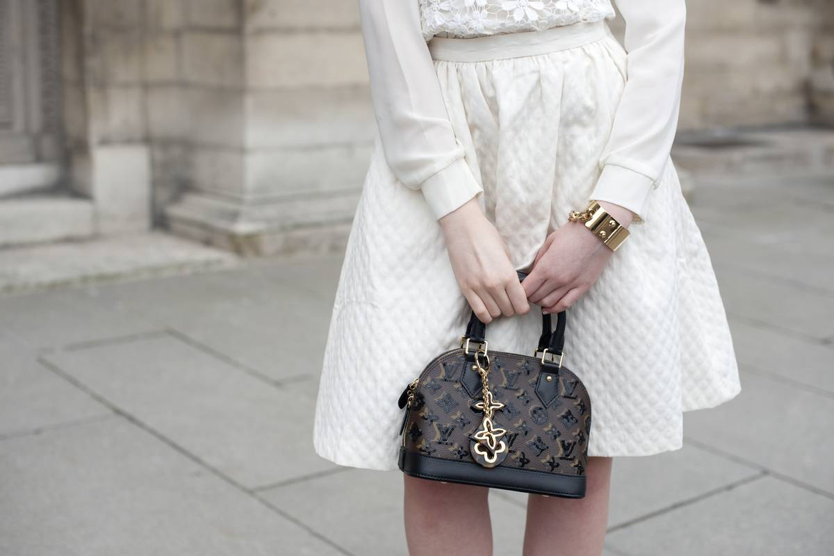 A fashion blogger holds a Louis Vuitton purse.