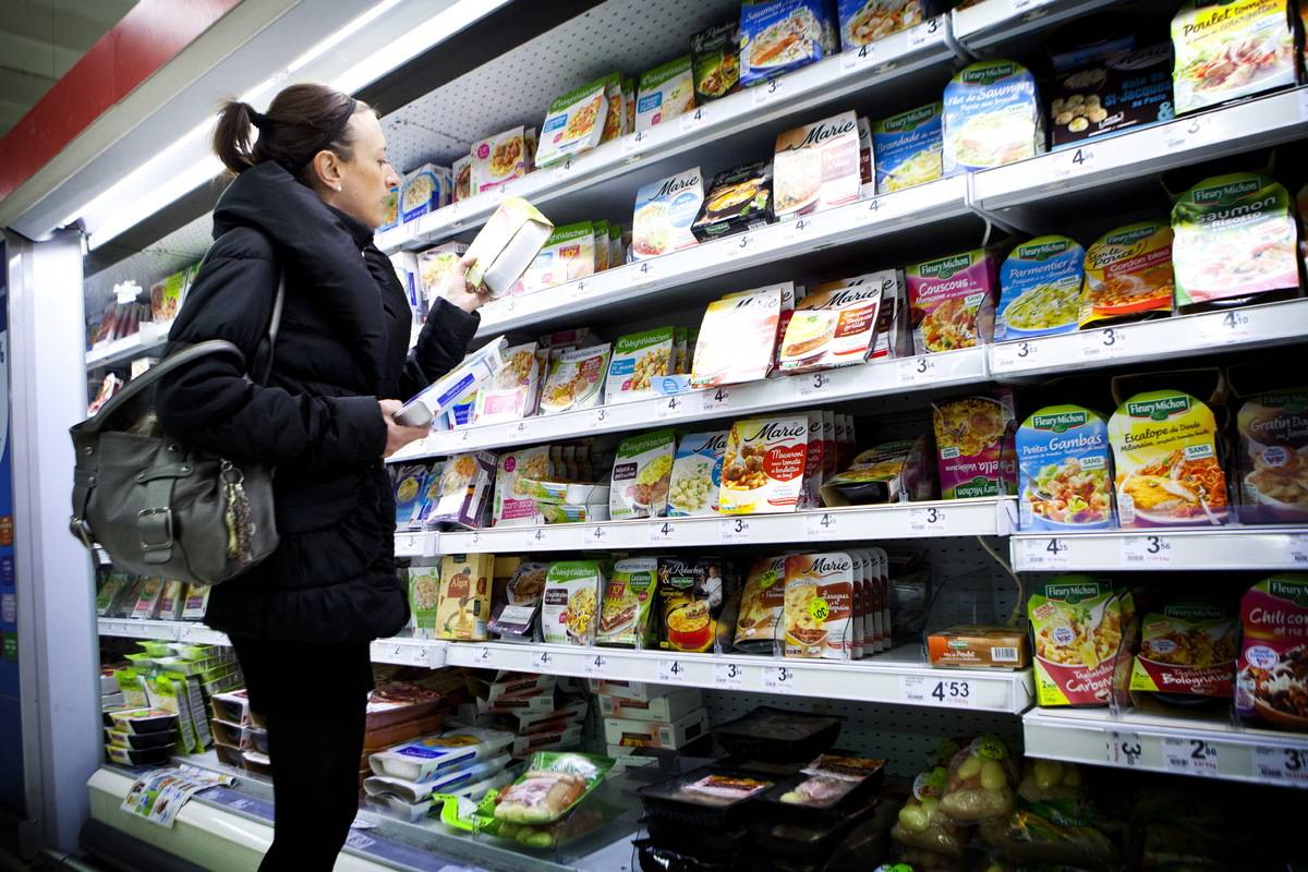 A woman reads the ingredients on packaged food at a grocery store.