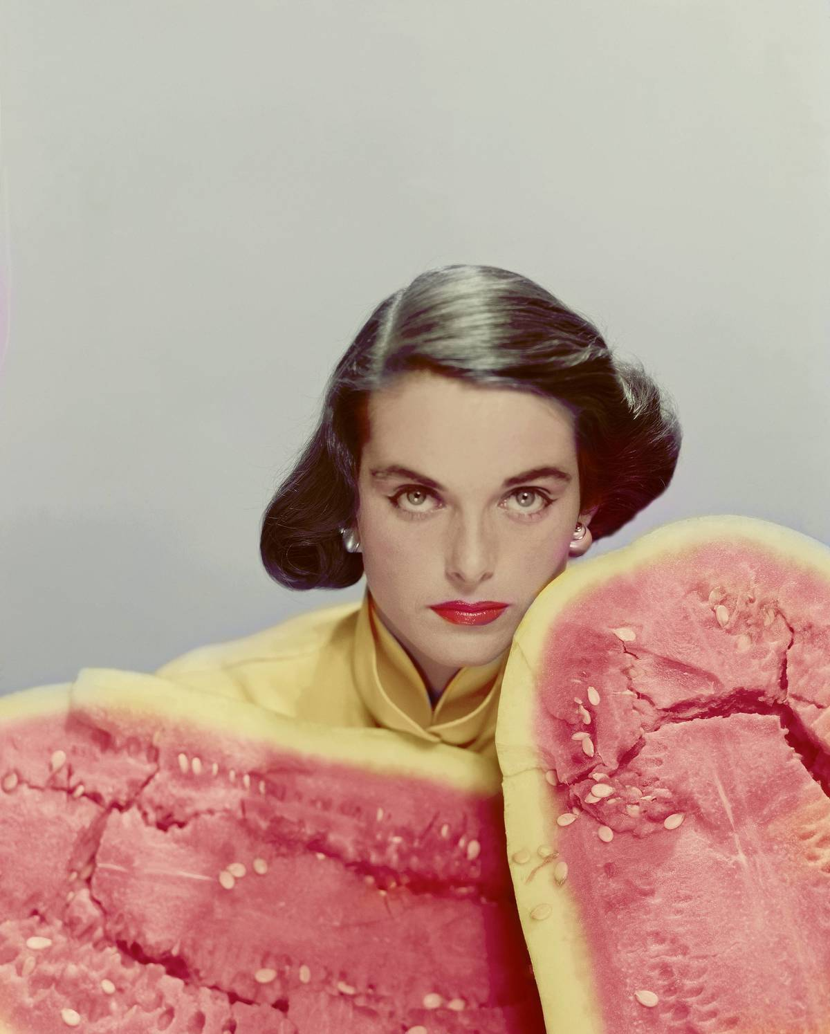 A model poses near giant slices of watermelon.