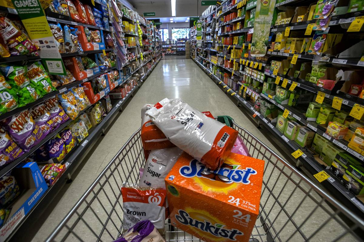 A shopping cart holds bags of sugar and soda.