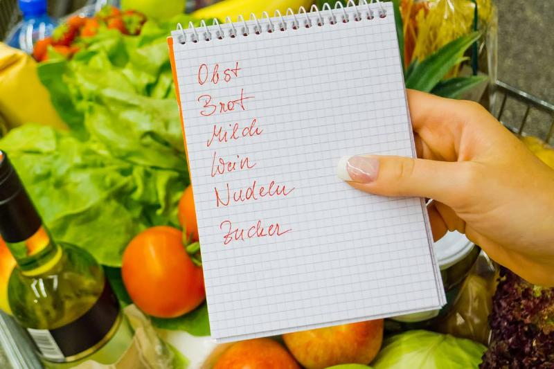 A woman in Germany holds a grocery list above produce.