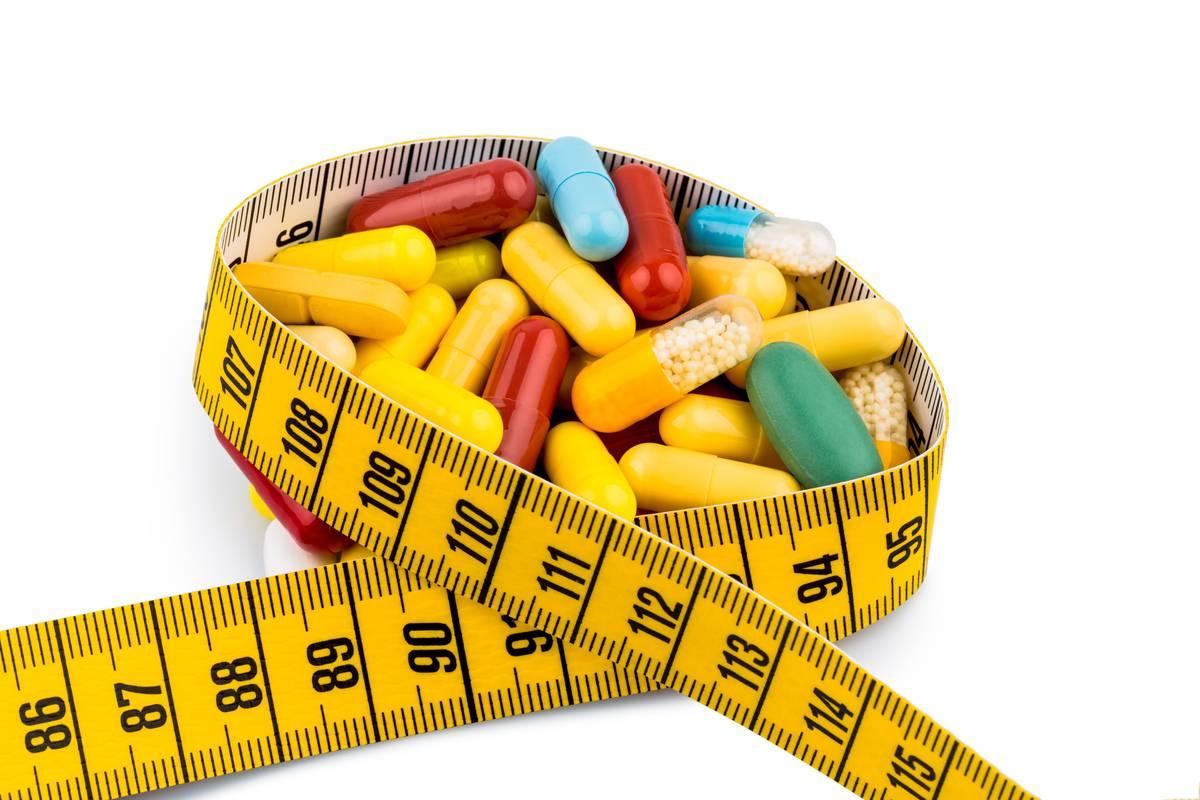 Measuring tape wraps around pill capsules.