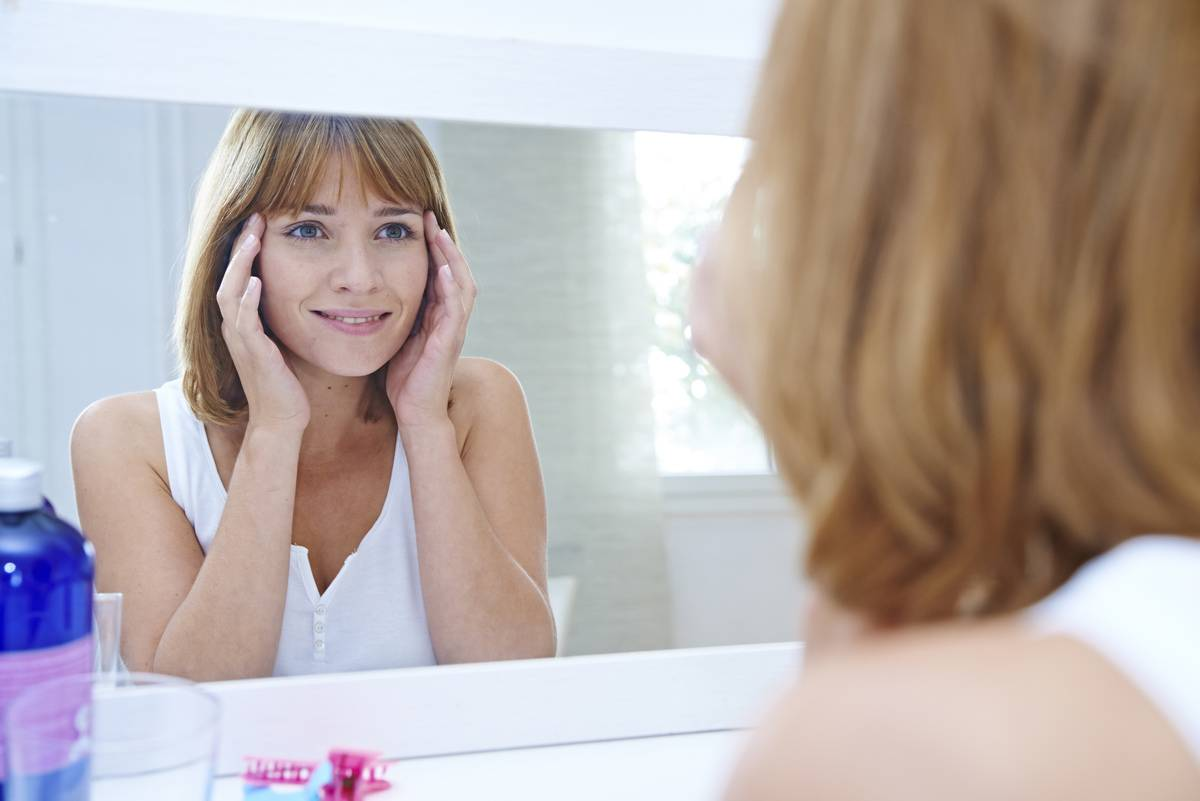 A woman examines her face in the mirror.
