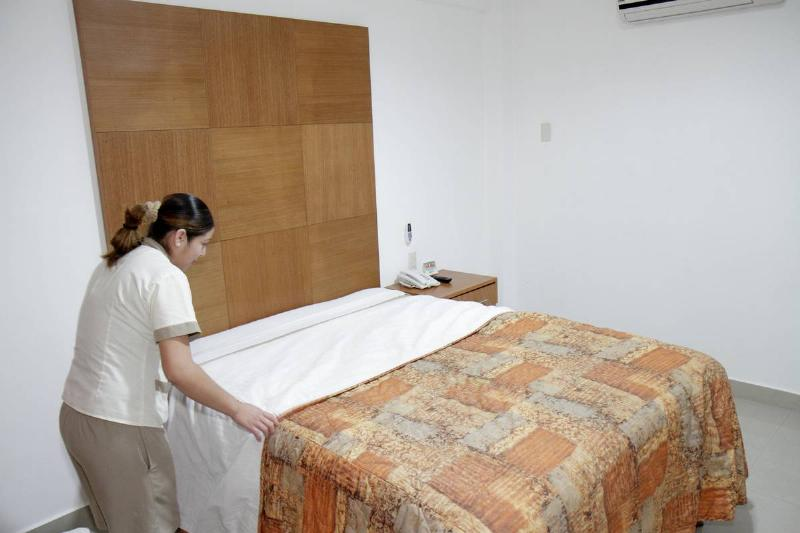 An employee makes a bed at a hotel.