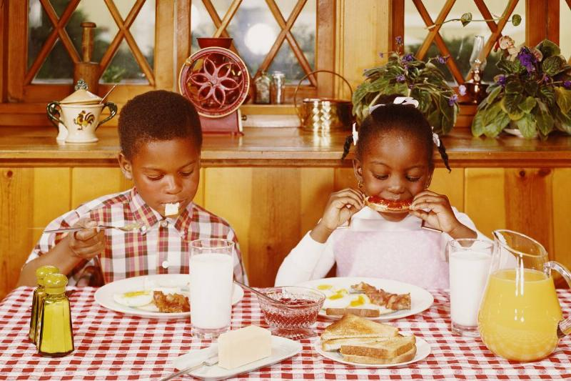 A boy and girl eat breakfast together.