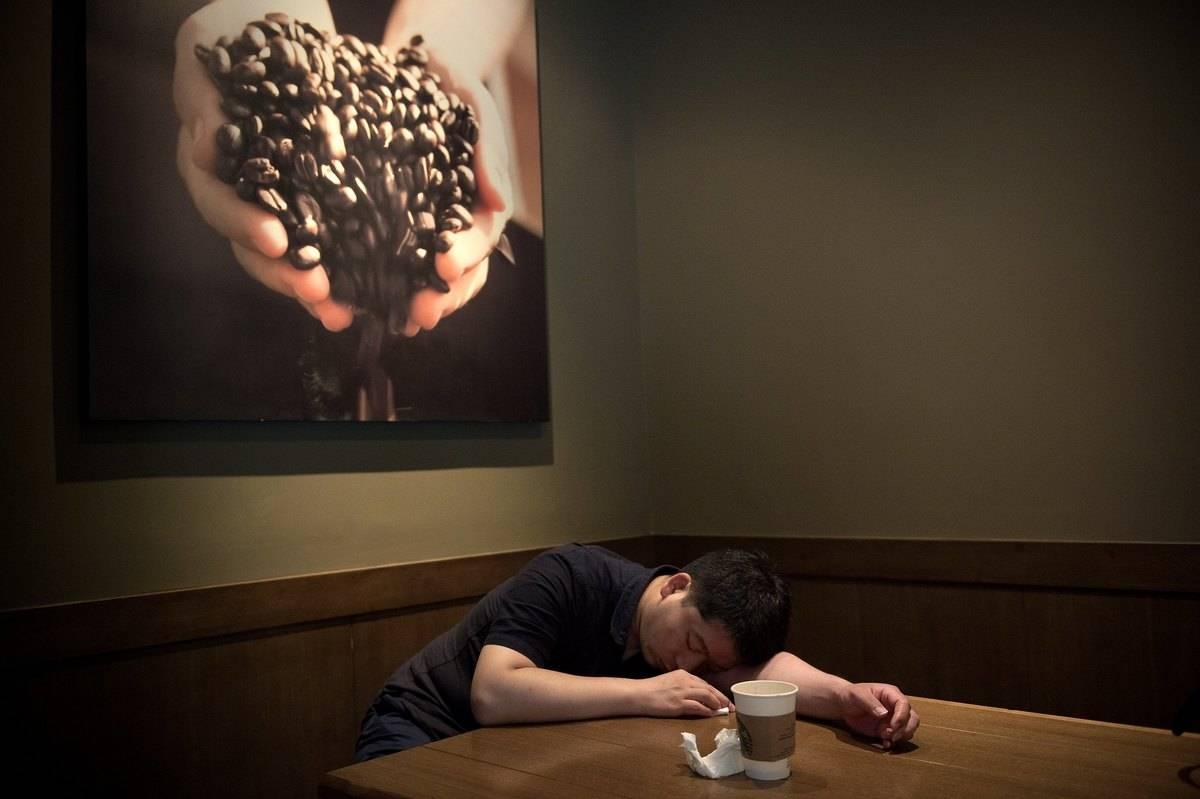 A man falls asleep in a Starbucks.