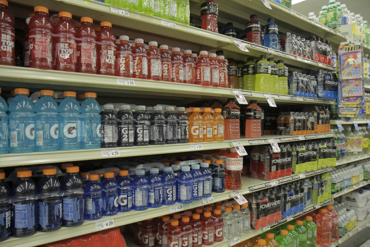 Sports drinks line the shelves of a supermarket.