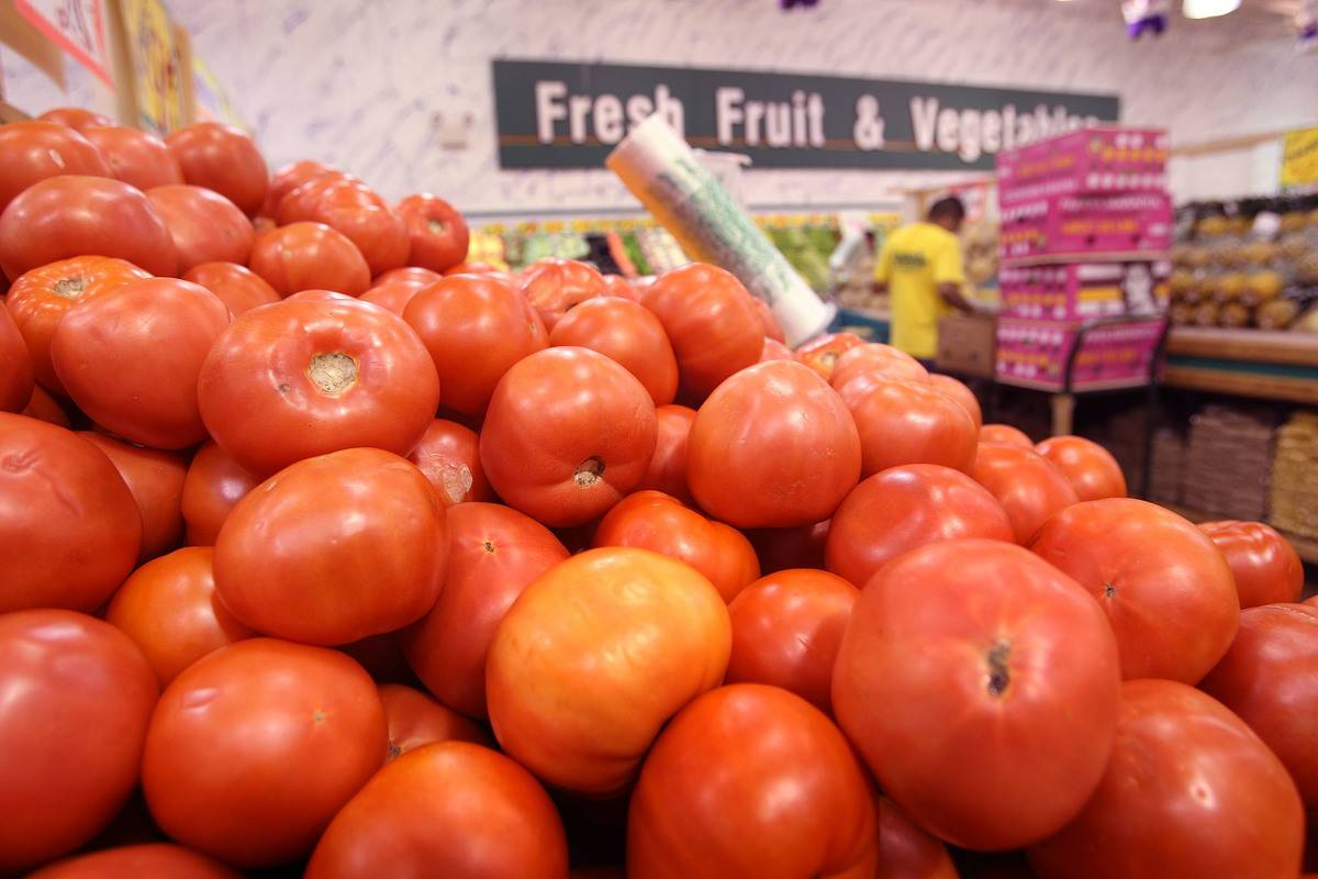 A pile of tomatoes are offered for sale.