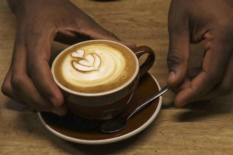 A server places a latte in a mug and saucer on a table.