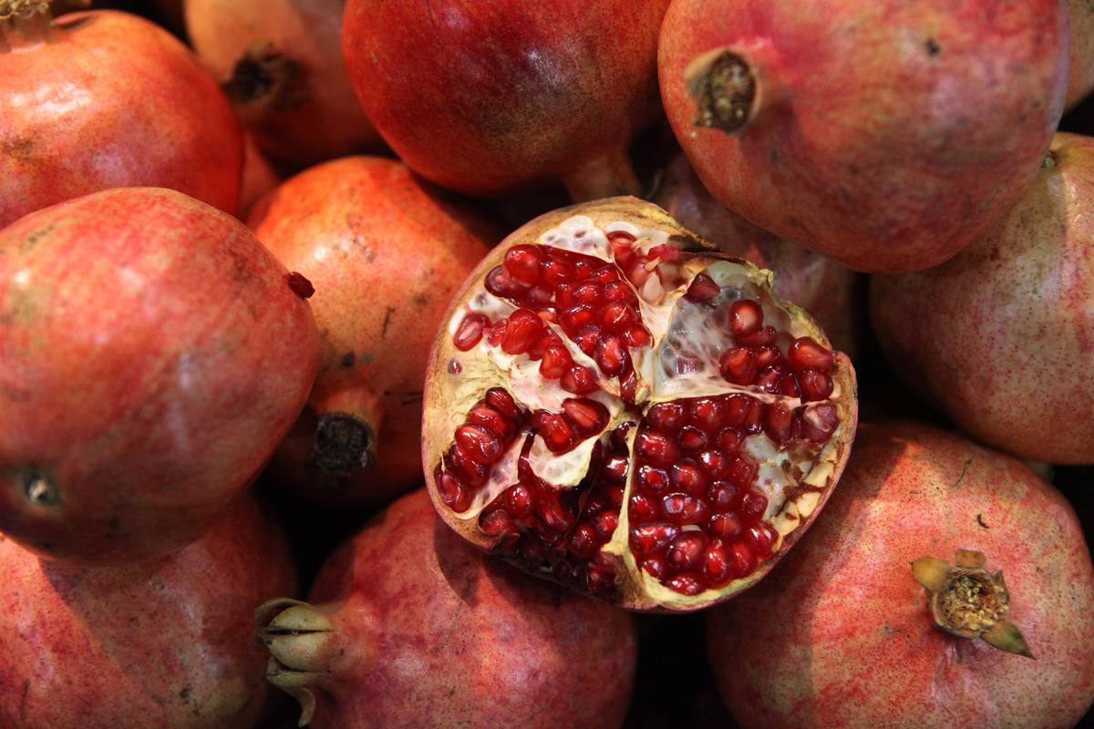 An open pomegranate sits on top of whole fruits.
