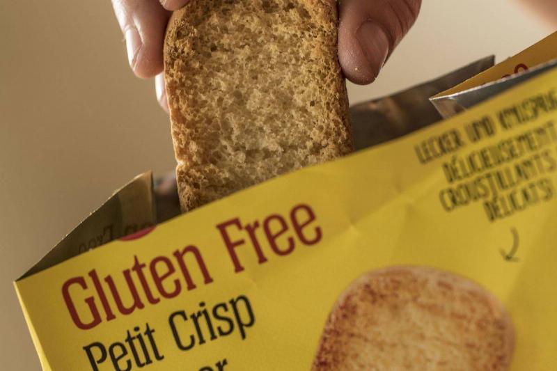 A woman pulls a gluten-free crisp bread out of a bag.