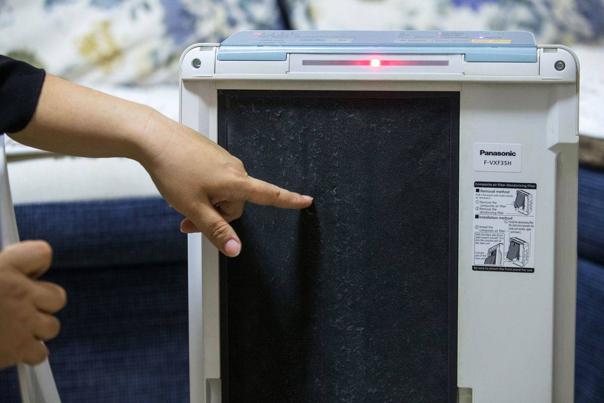 A person points to the filter on an air purifier.