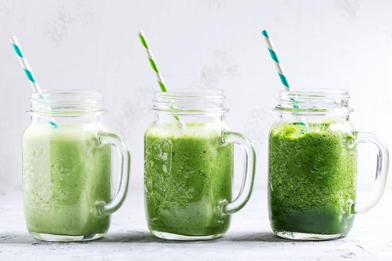 A green-colored smoothie is in three mason jars with straws.
