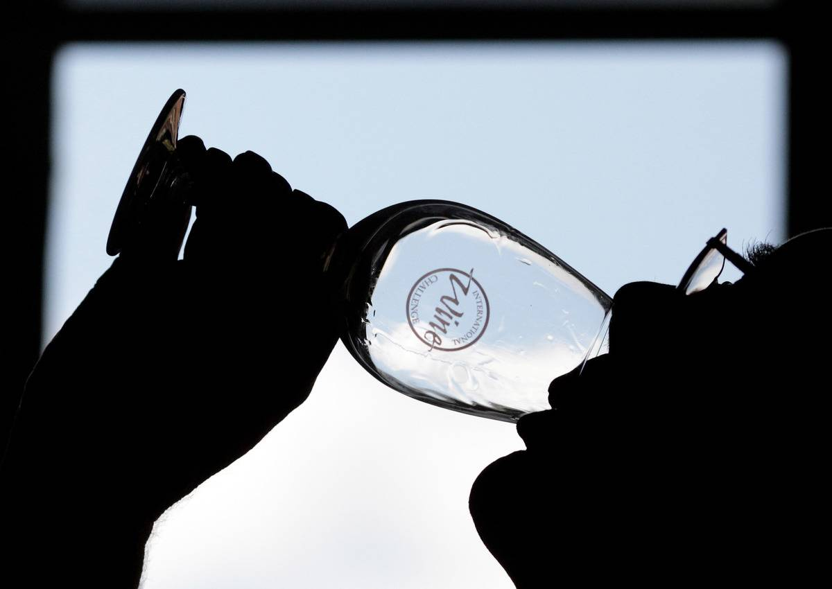 A judge drinks from a wine glass during an International Wine Challenge.