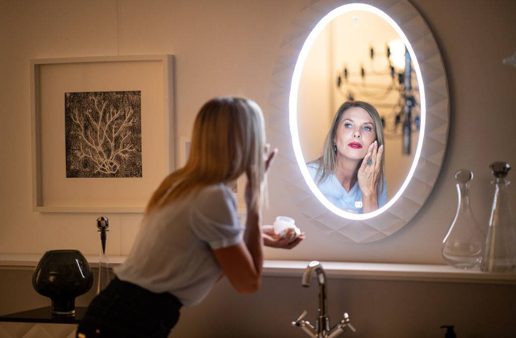 woman putting on makeup in front of the bathroom mirror