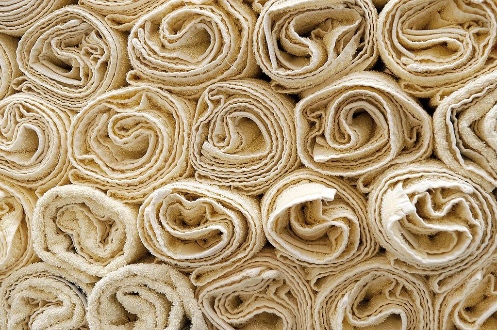 several tan towels rolled up and stacked