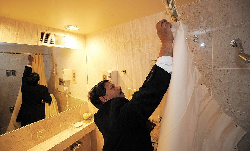 man removing a shower curtain