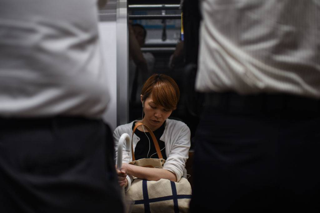 Woman sleeping in subway, Tokyo, Japan.