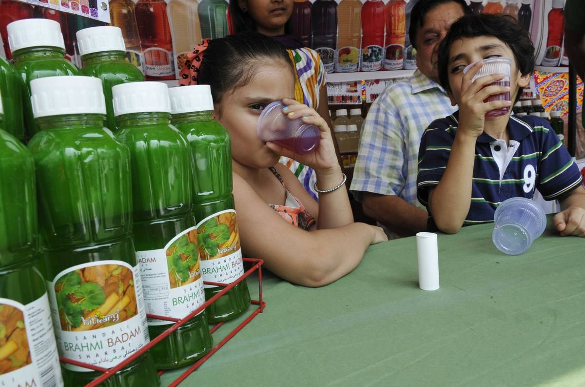 Kids drink Aam Panna in a cafe.