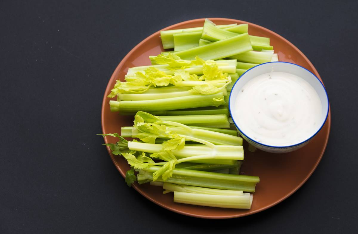 Celery sticks with leaves on few of them and a bowl full of ranch.