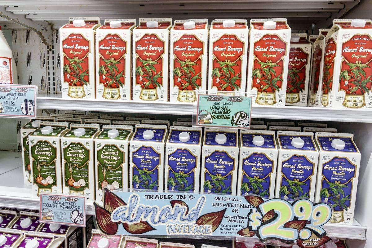 Cartons of almond milk are lined on grocery store shelves.