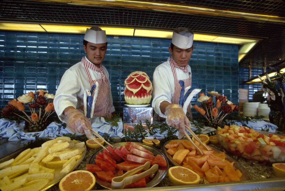 Chefs serve buffet style fruit on a cruise.