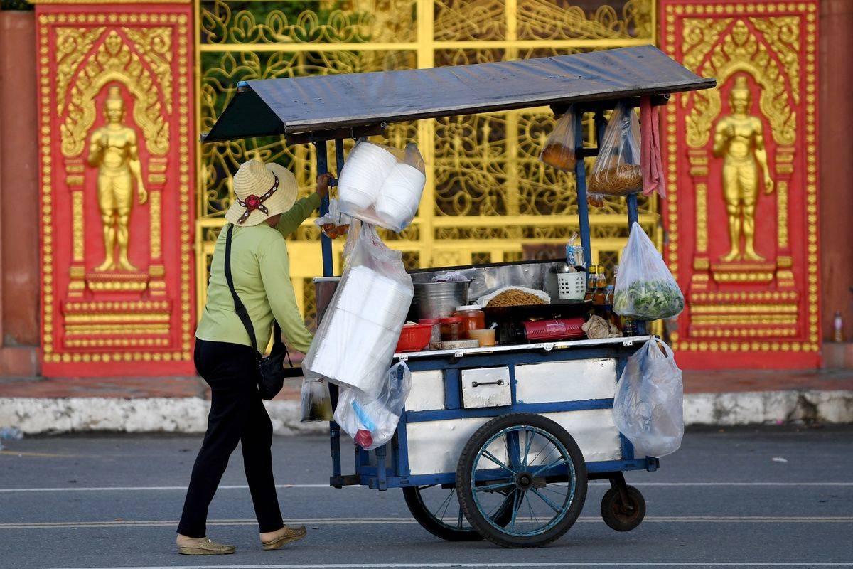 A vendor pushes a food cart across the street.