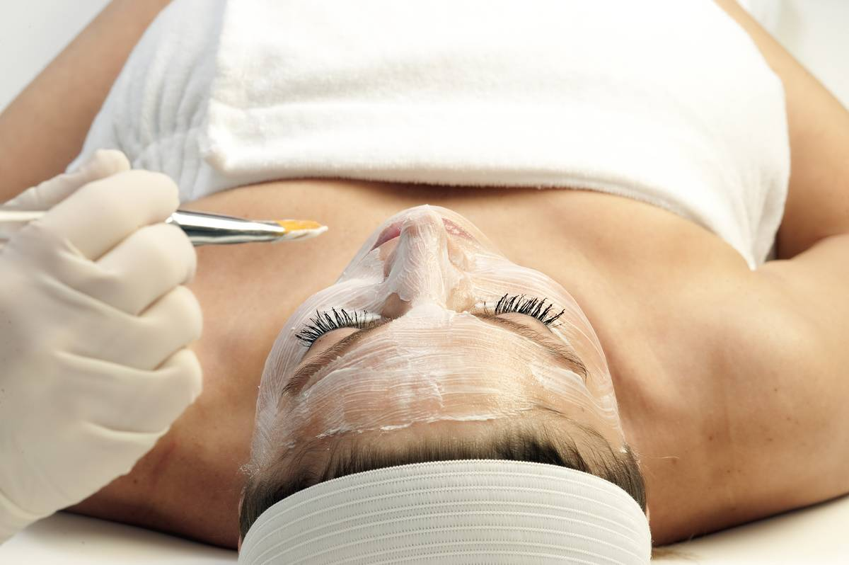 A woman receives a facial treatment at a spa.