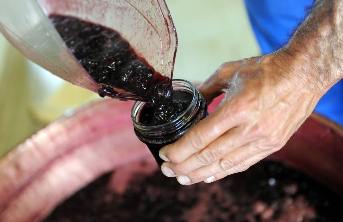 A man pours jam into a glass jar.