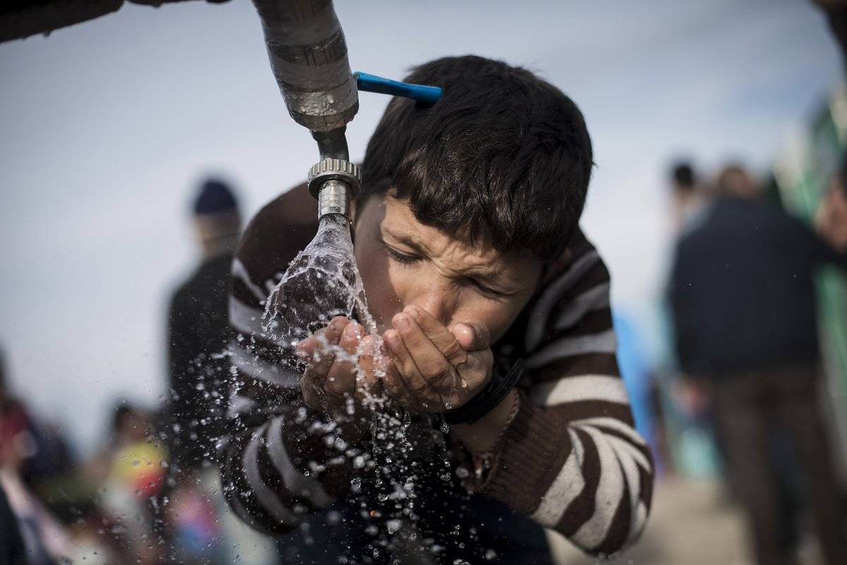 A boy drinks water from a faucet in Greece.