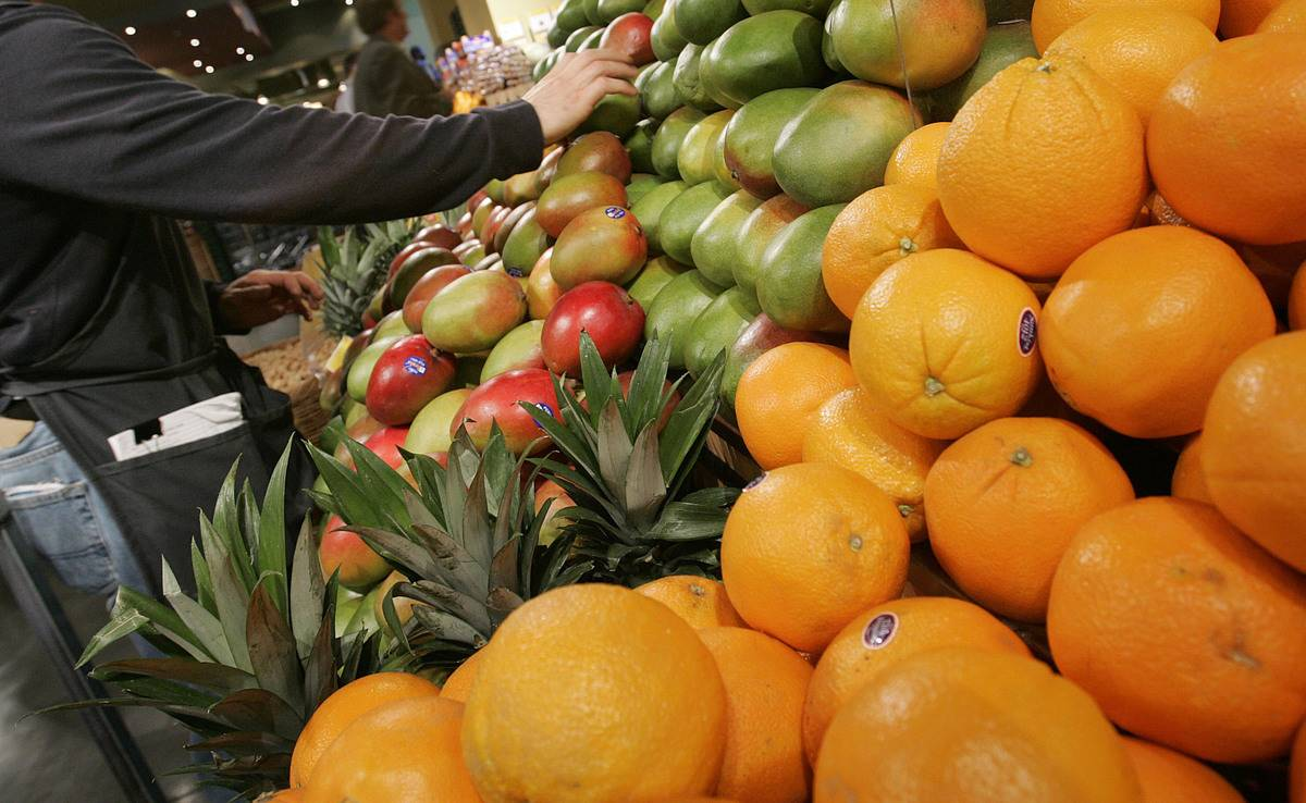 A person selects fruits for sale.