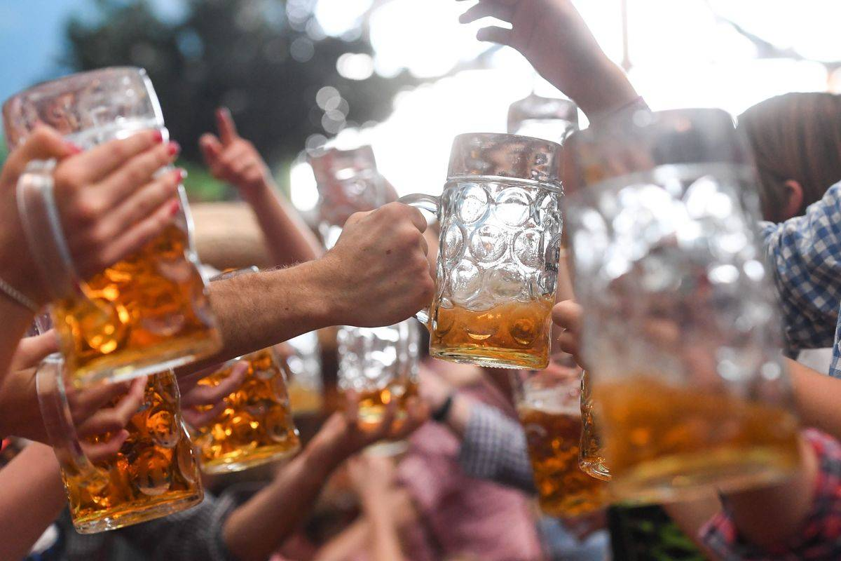 People in Germany toast with mugs of beer during Oktoberfest.