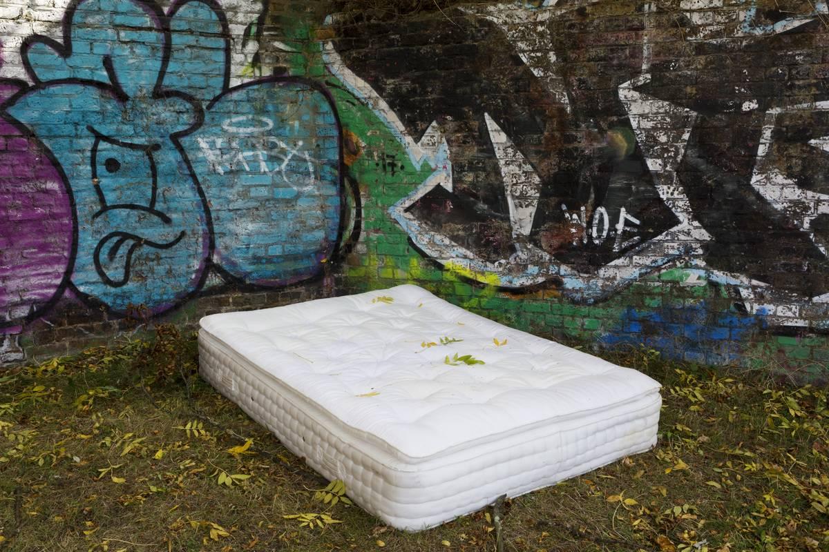 An abandoned mattress lies in front of a graffitied wall.