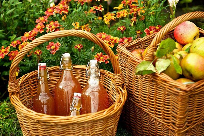 apple cider in a basket next to a basket of apples in front of flowers