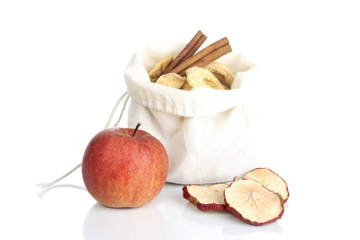 An apple is next to a bag of dried apple slices and cinnamon sticks.