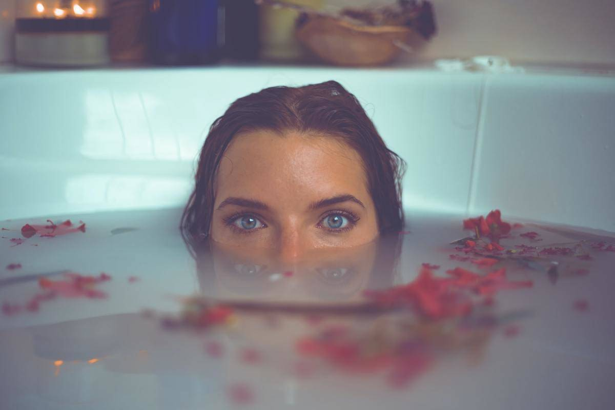 A woman submerges half of her face in a milky bath with rose petals.