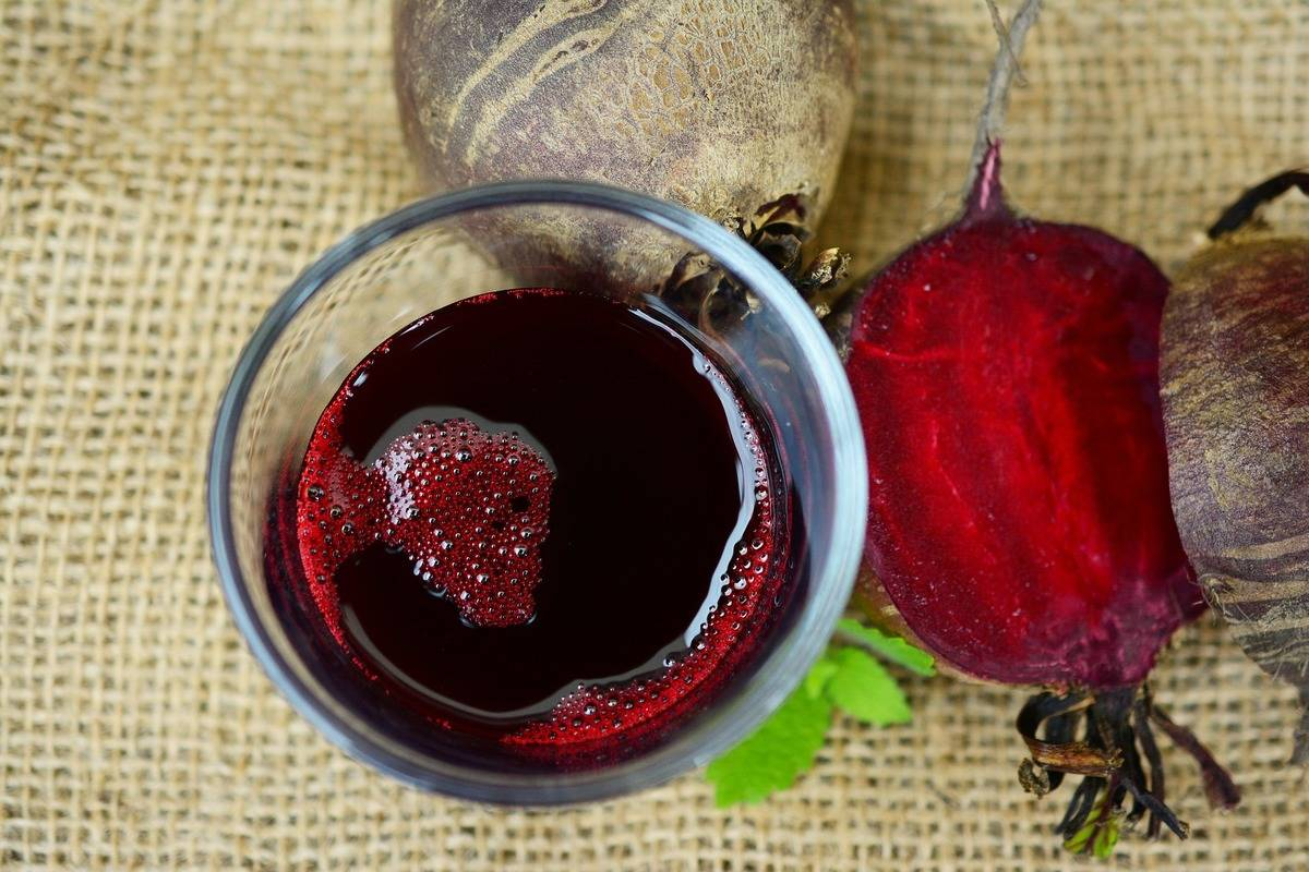 A cup of beetroot juice is viewed from above with sliced beets and mint.